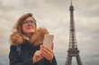 Using cellphone with Eiffel tower, Paris in the background.