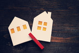 Two lodges from white paper on a wooden background. Symbol of the house, family, cosiness. Concept image house. Concept of sale or purchase house - 128967622