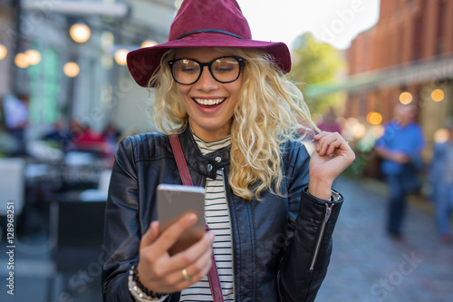 Happy and funny woman looking at her phone