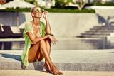 Fashion portrait of young tanned model woman in bikini and sungl