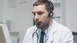 Male Doctor Consults Patients on the Internet. He Sits before His Personal Computer and Wears Microphone. Shot on RED Cinema Camera in 4K (UHD).