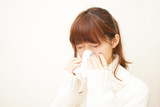 Young woman blowing her nose with tissues