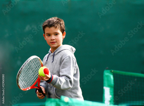 Fotobehang Tennis Little tennis player on a blurred green background