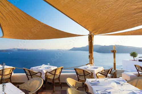 Foto Spatwand Santorini restaurant on terrace with view on sea, Santorini island, Cyclades, Greece