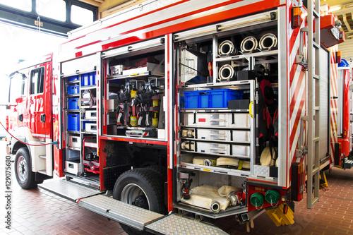 Sprzęt gaśniczy w wozie strażackim z garażem pojazdu otwartym na głównym posterunku policji
