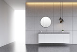 Bathroom sink with round mirror on tiled wall, concrete floor