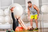 Fototapety Young woman making exercise with fitball with personal trainer in the fitness room