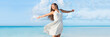 Leinwanddruck Bild Freedom young woman with arms up outstretched to the sky with blue ocean landscape beach background copy space. Banner panorama. Asian girl in white dress dancing carefree in sunset.