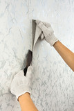 hands removing old wallpaper with spatula - 129112287