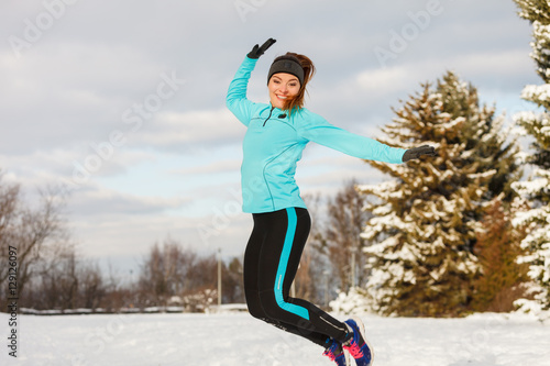 Poster Young girl jumping in the snow.