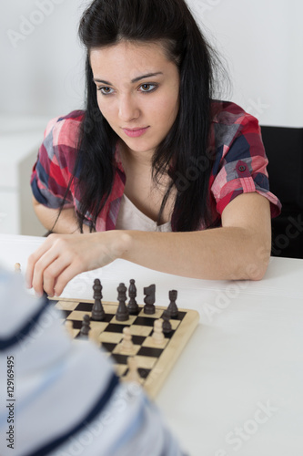 Poster portrait of a beautiful brunette young woman playing chess