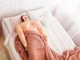 Sex doll lies under blanket on bed. - 129171011