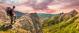 Hiker on the top enjoys mountains panorama landscape before sunrise