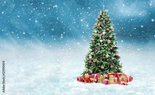 Geschmückter Christbaum mit Geschenken im Schnee - 129190434