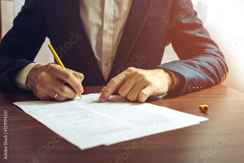Mężczyzna biznesmen podpisuje dokumenty za pomocą pióra