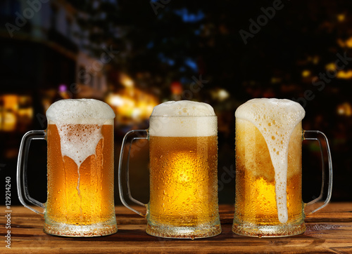 Fototapeta cold glass mug of beer with foam on the background of the street