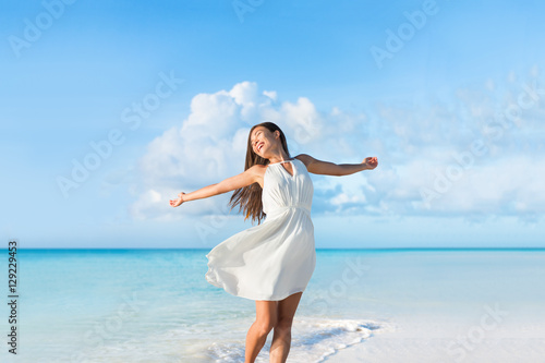 Leinwanddruck Bild Freedom young woman carefree and happy with open arms on blue ocean landscape beach background. Asian girl in white dress feeling happiness enjoying her travel vacation.