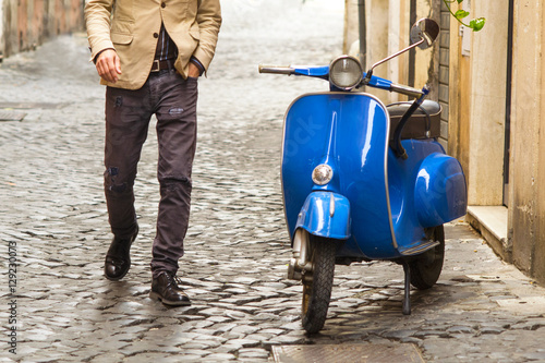 Foto op Canvas Scooter uomo che si dirige verso uno scooter vintage a Roma