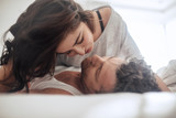 Young couple caressing lying in bed - 129235837