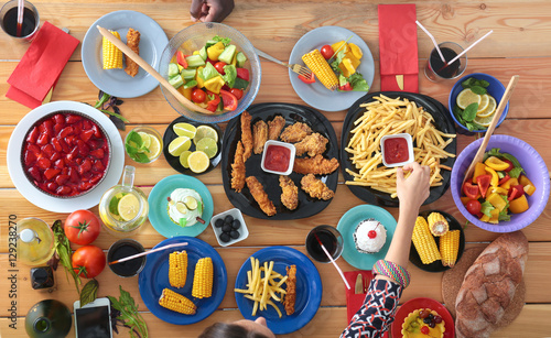 Top view group of people having dinner together while sitting at wooden table - 129238270