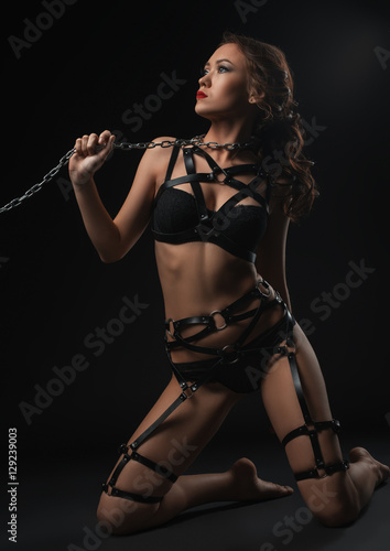 Girl in underwear and belts posing on her knees