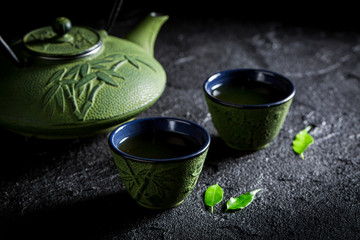 Green tea with teapot and cup on black rock