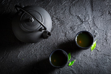 Aromatic green tea with teapot and cup on black rock