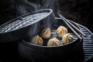 Homemade and hot manti dumplings in wooden steamer