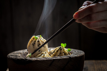 Tasty and hot chinese dumplings in wooden bowl