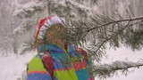 Woman in Cap Santa Knocks Snow From Trees in Forest