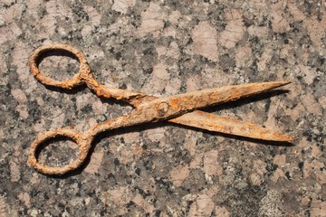 Old rusty scissors on a granite countertop. Old tool tailor.