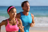 Couple runners running on beach. Interracial young adults asian woman, caucasian man, training cardio together doing outdoor workout jogging.