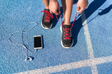 Running motivation music on mobile phone runner woman tying shoe laces. Shoes and feet closeup, athlete getting ready for race or workout on run track with smartphone and earphones.