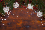 Christmas wooden background with branches of a Christmas tree, confetti, with snowflakes, pine cones. New Year.