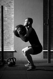 Fototapety Muscular hard working man squatting with a med ball