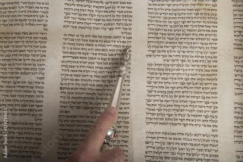 hand of a man reading an ancient torah scroll Canvas Print
