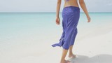 Woman on beach travel vacation lifestyle concept. Girl walking by ocean on holidays under blue clear summer sky on tropical beach. RED EPIC SLOW MOTION.