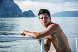 Portrait of young handsome bare-chested brunet manlooking away against seascape on a boat or ship, leaning on handrail.