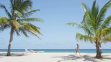 Beach with palm trees on against clear blue sky. Woman walking in idyllic nature travel vacation holiday tourist destination beach on Barbados, Caribbean. RED EPIC SLOW MOTION.