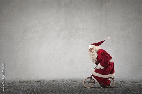 Poster Santa Claus riding a small bike