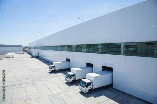 fasada budynku przemysłowego i magazynu z długimi wagonami towarowymi