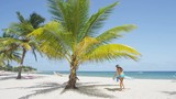 Woman on beach putting down beach towel for sunbathing under palm tree. Girl wearing bikini and sun hat relaxing on beach on Barbados, Caribbean. RED EPIC SLOW MOTION.