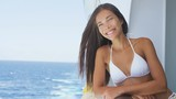 Happy girl in bikini laughing enjoying cruise ship travel vacation at sea. Mixed race Asian Chinese / Caucasian woman traveling on cruise liner enjoying herself on her balcony. RED EPIC SLOW MOTION.