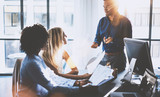 Young team of coworkers making great meeting discussion in modern coworking office.Hispanic businessman talking with two beautiful womans.Teamwork process.Horizontal,blurred background,flares effect.