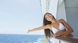 Happy woman in bikini cheering joyful enjoying cruise ship travel vacation. Mixed race Asian Chinese / Caucasian woman traveling on cruise liner excited and cheerful on balcony. RED EPIC SLOW MOTION.