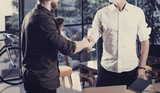 Concept of business partnership handshake.Closeup photo two businessmans handshaking process.Successful deal after great meeting in coworking studio.Horizontal, blurred background.