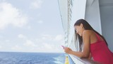 Smartphone woman texting on social media app on cruise ship travel vacation looking at display screen for sms reading on ocean background on balcony. Girl using smart phone on holiday. RED EPIC.