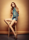 lifestyle, fashion and people concept: Full body portrait of  fashion model sitting on wood chair in studio