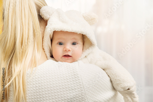 Poster mother with her baby in fluffy bear costume over shoulder