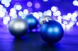 Leinwandbild Motiv Blue christmas ball and blured purple lights at the background